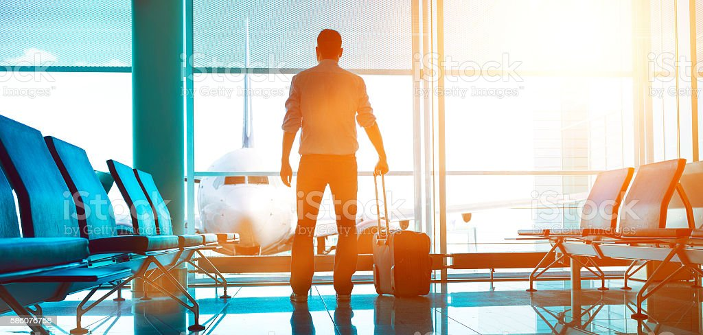 Businessman stands in airport terminal ready to board airplane stock photo