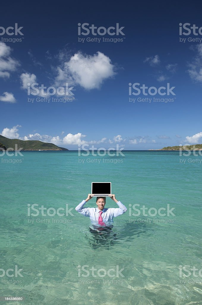 Businessman Stands in Deep Water with Laptop on Head royalty-free stock photo