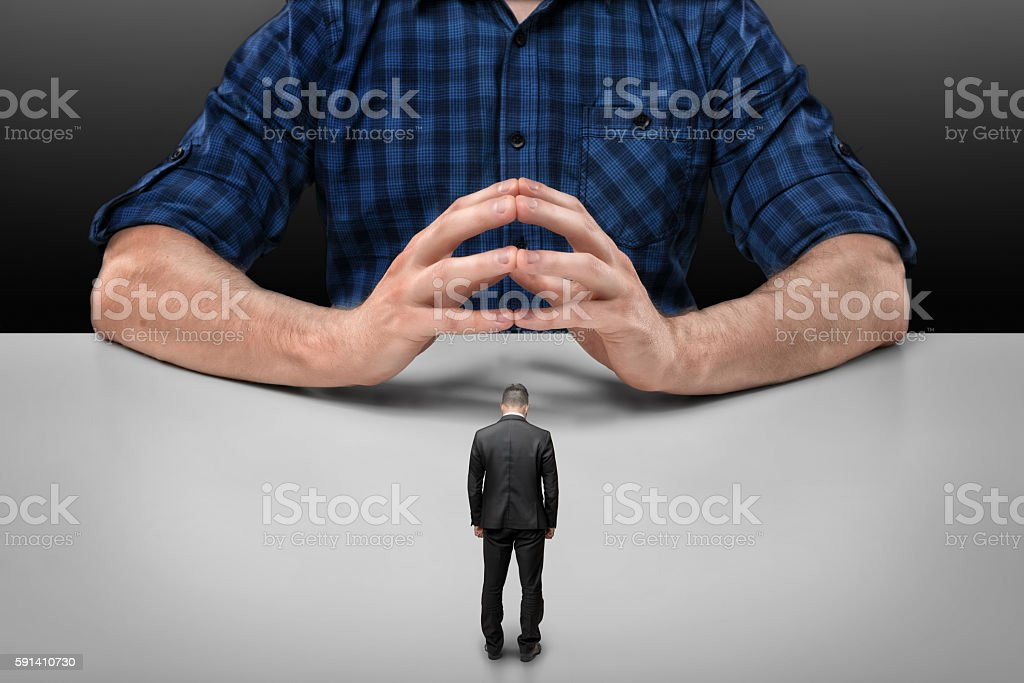 Businessman stands in front of big man sitting with his stock photo