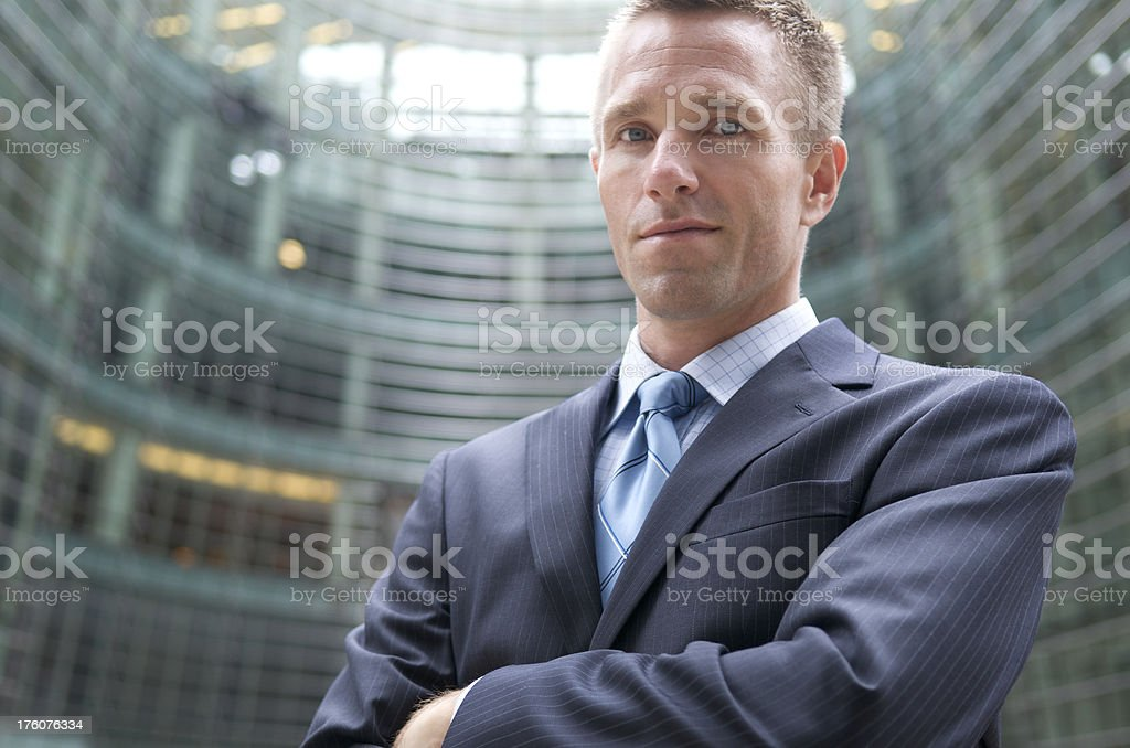 Businessman Stands in front of Curved Office Block royalty-free stock photo