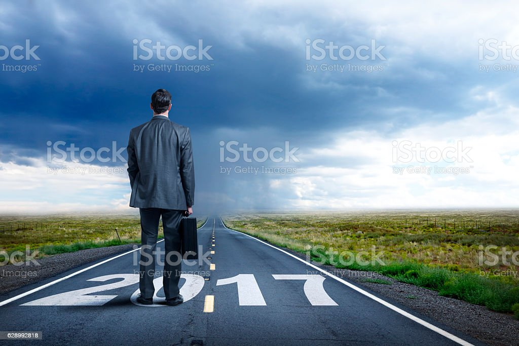 Businessman Stands On Long Road With 2017 Painted On It stock photo