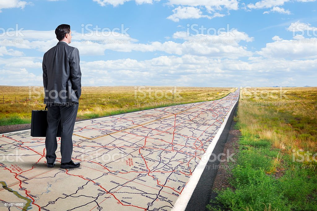 Businessman Stands On Long Road With Road Map Painted On It stock photo