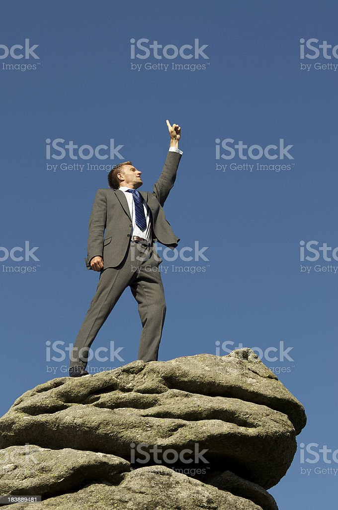 Businessman Stands on Mountaintop Pointing to the Sky royalty-free stock photo
