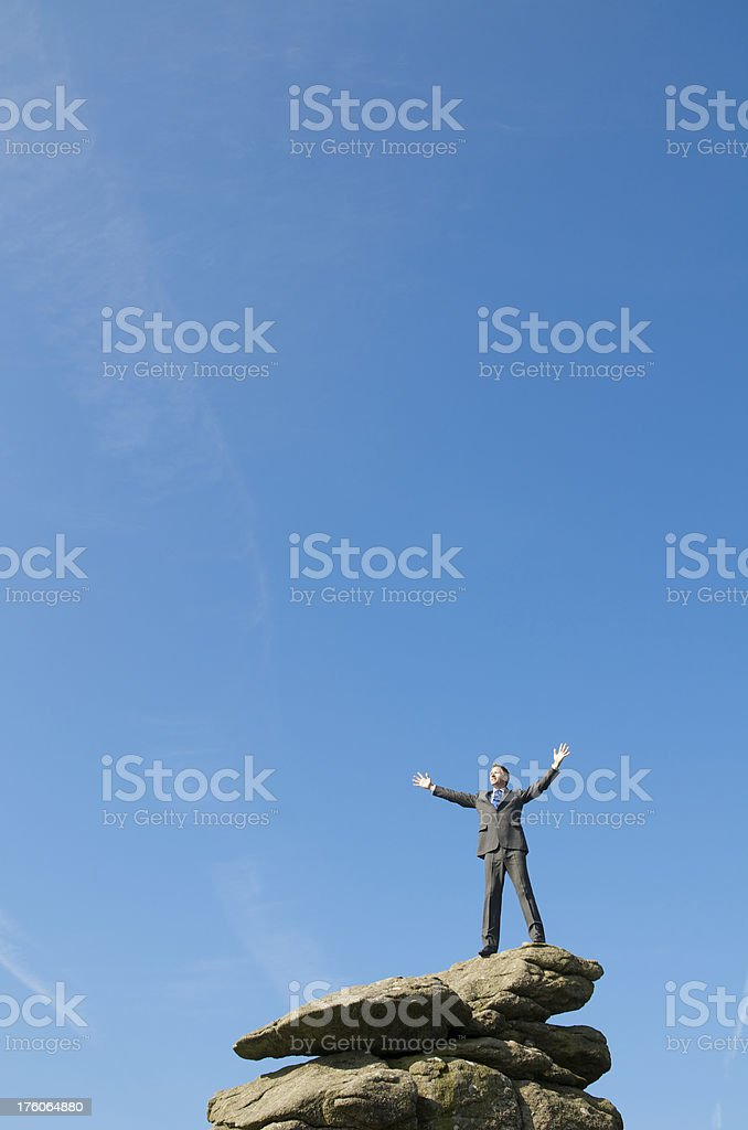 Businessman Stands w Arms Outstretched On Rock royalty-free stock photo