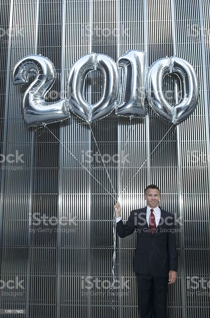 Businessman Stands w Shiny Silver 2010 Balloons royalty-free stock photo