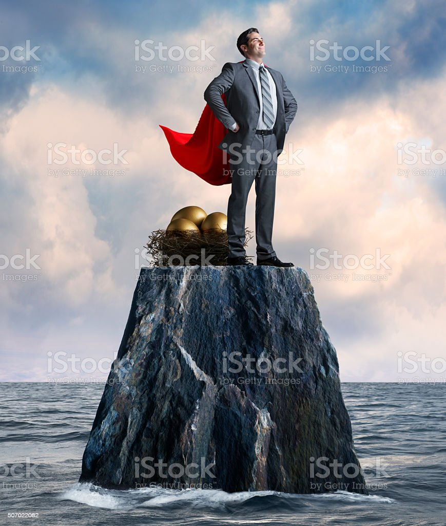 Businessman Stands While Protecting His Nest Egg On Isolated Island stock photo