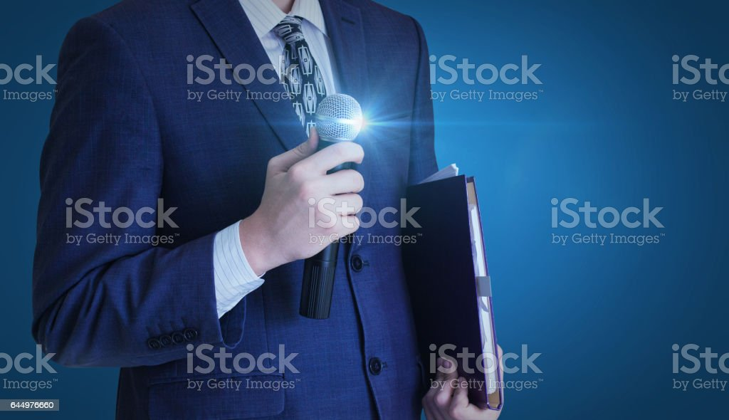 Businessman stands with a microphone. stock photo