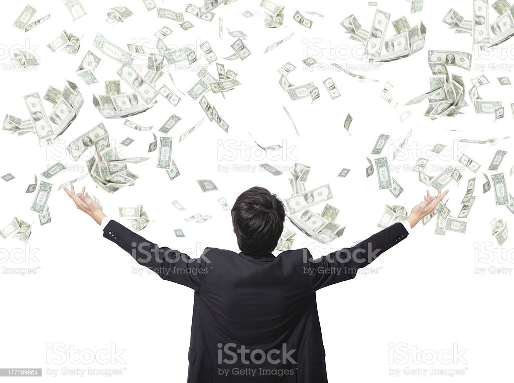 Businessman stands with arms out as money falls stock photo