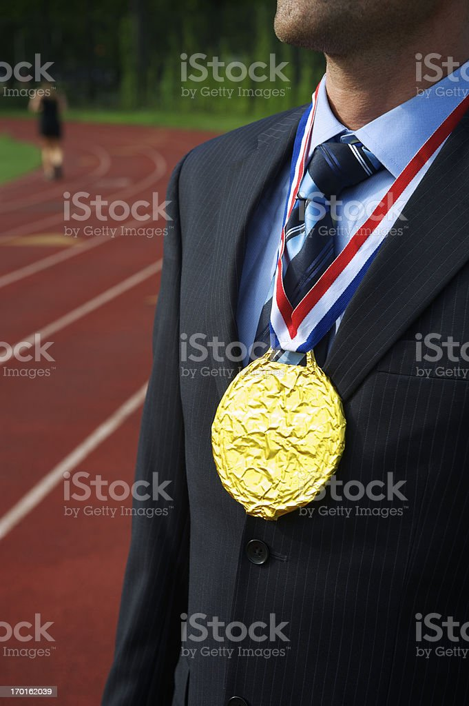 Businessman Stands with Gold Medal Next to Running Track royalty-free stock photo