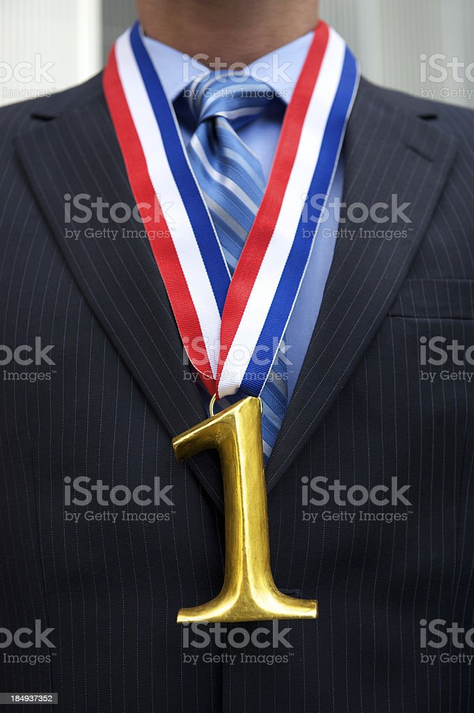 Businessman Stands with Gold Medal Number One royalty-free stock photo