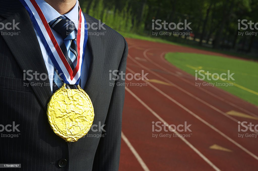 Businessman Stands with Gold Medal Outdoors Next to Running Track royalty-free stock photo