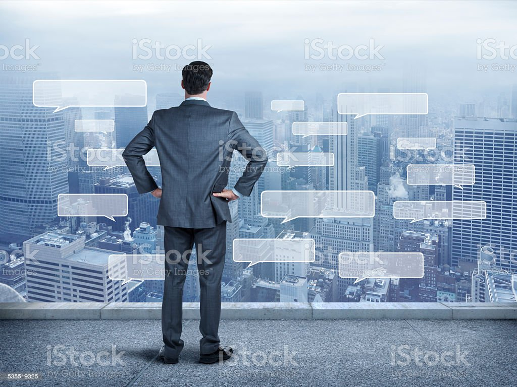Businessman staring at a large city full of text bubbles stock photo