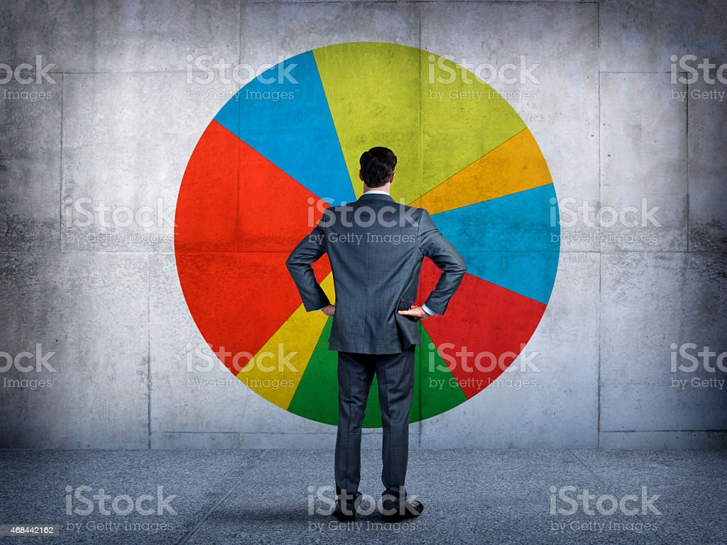 Businessman staring at a pie chart on a wall stock photo