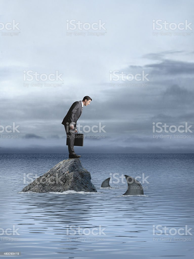 Businessman staring at sharks that circle rock he stands on stock photo