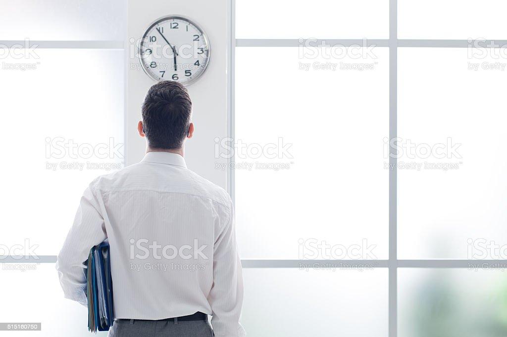 Businessman staring at the clock stock photo