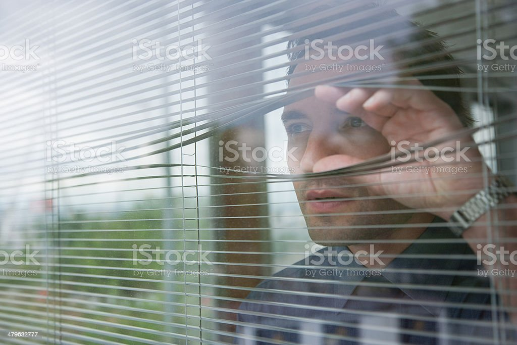 Businessman staring out office window stock photo