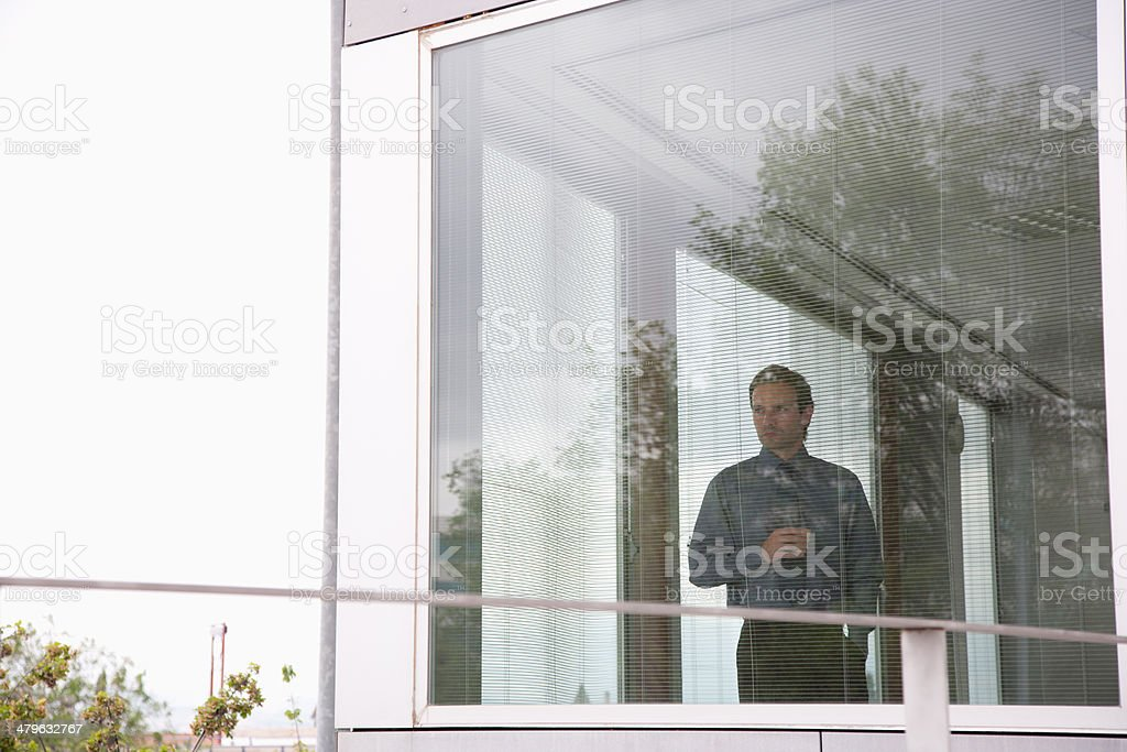 Businessman staring out office window with coffee stock photo