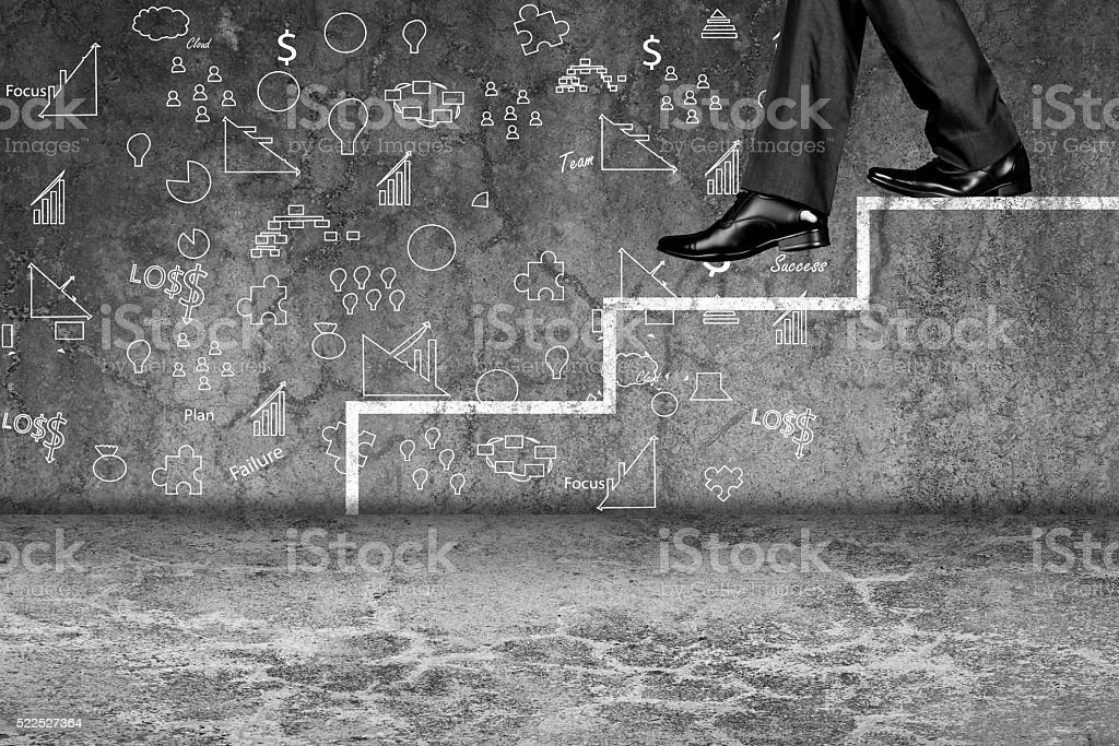 Businessman stepping down on ladder stock photo