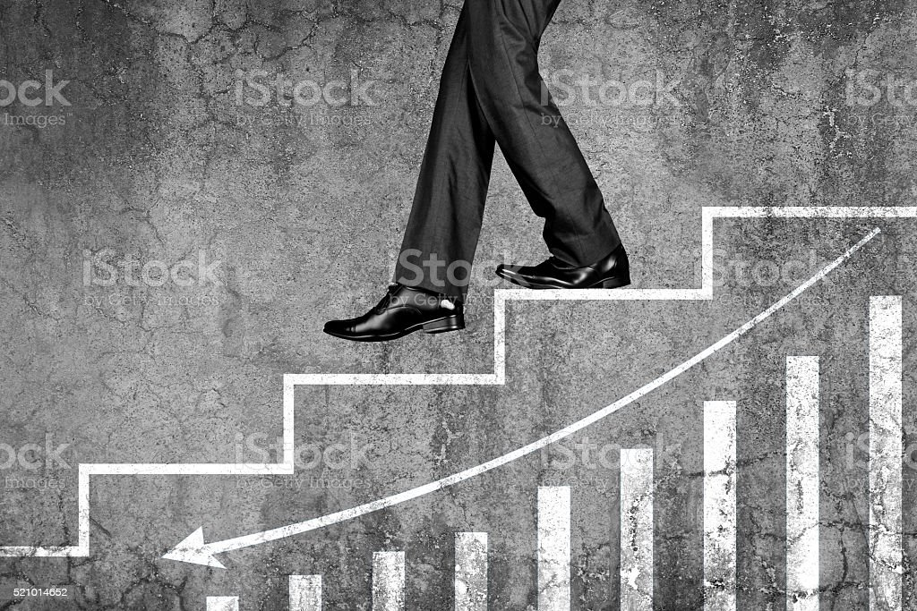Businessman stepping down on steps with graph chart stock photo