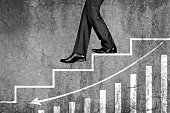 Businessman stepping down on steps with graph chart