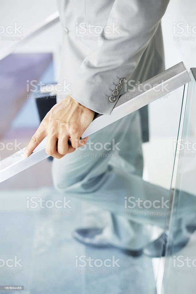 Businessman stepping down the stairs with briefcase in hand stock photo