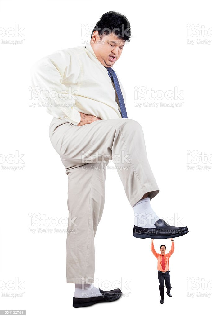 Businessman stepping foot over his rival stock photo