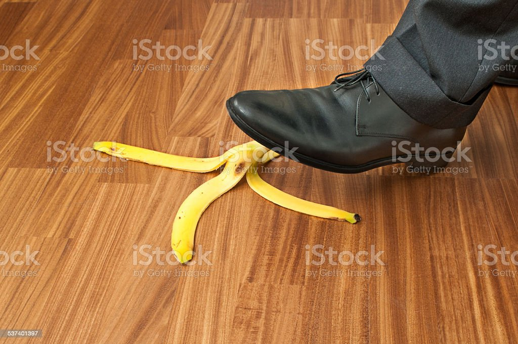 Businessman stepping on banana peel stock photo