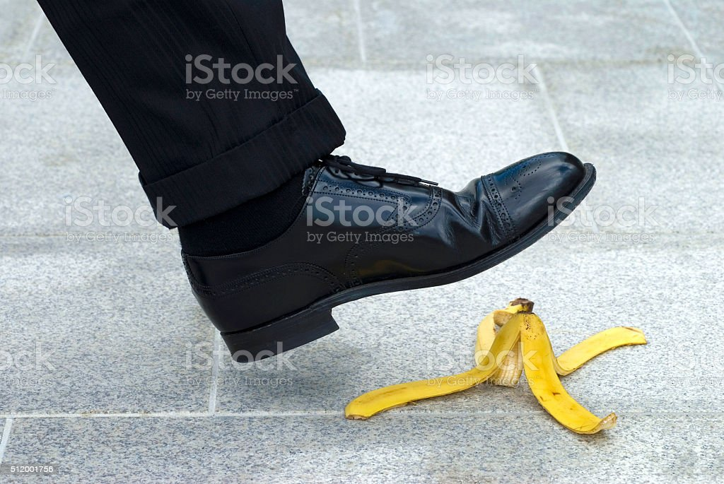 Businessman stepping on banana skin stock photo