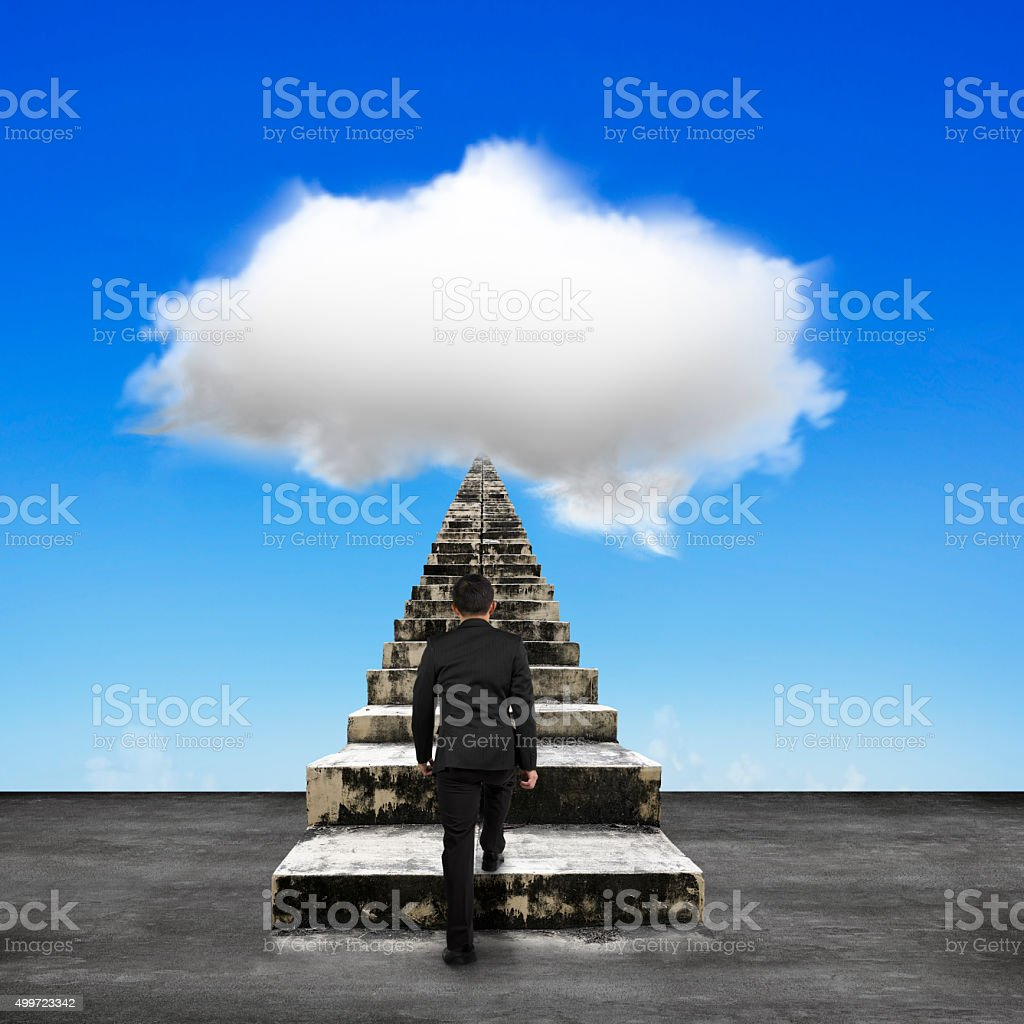 Businessman steps up old concrete stairs toward white cloud stock photo