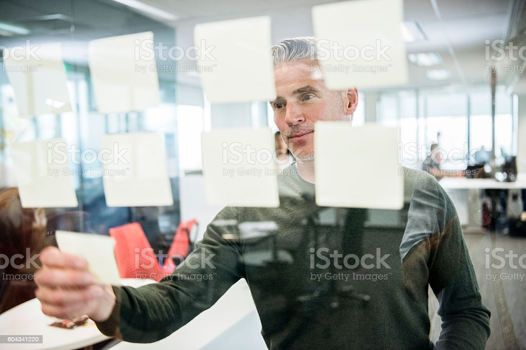 Businessman sticking notes on window in office stock photo