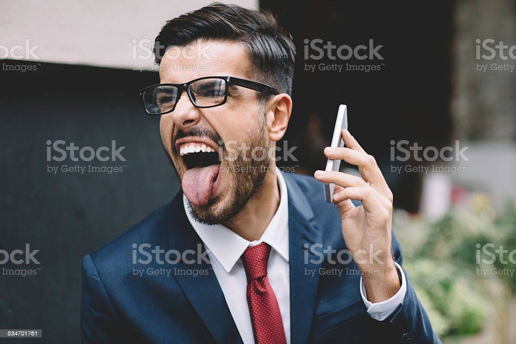 Businessman sticking out tongue at the street stock photo
