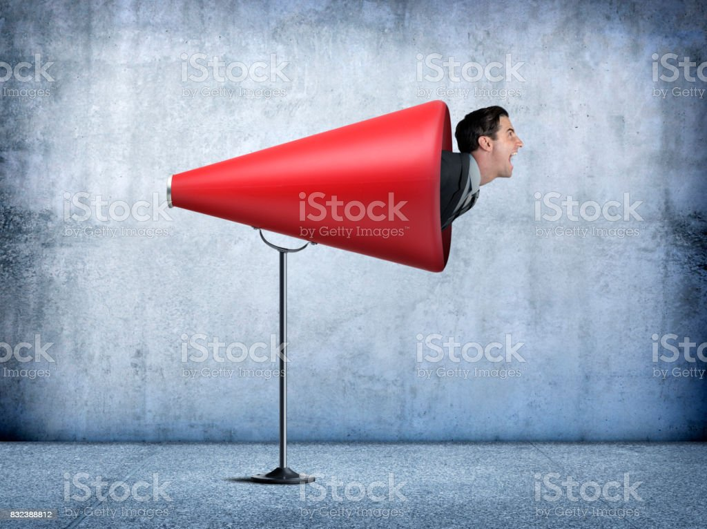 Businessman Sticks His Head Out Of A Large Red Megaphone stock photo