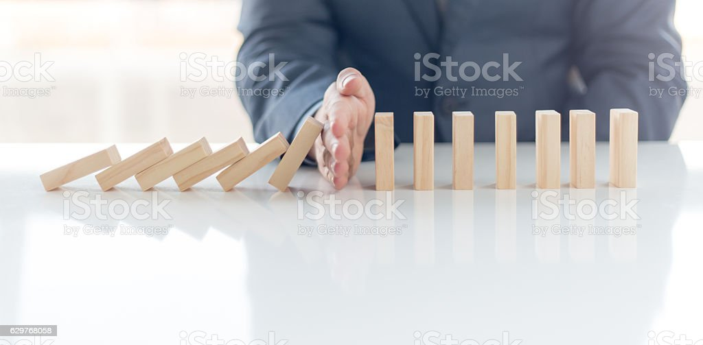 Businessman Stop Domino Effect. Risk Management and Insurance Concept stock photo