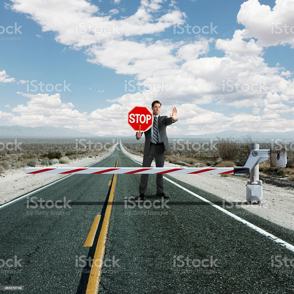 Businessman stopping traffic at roadblock stock photo