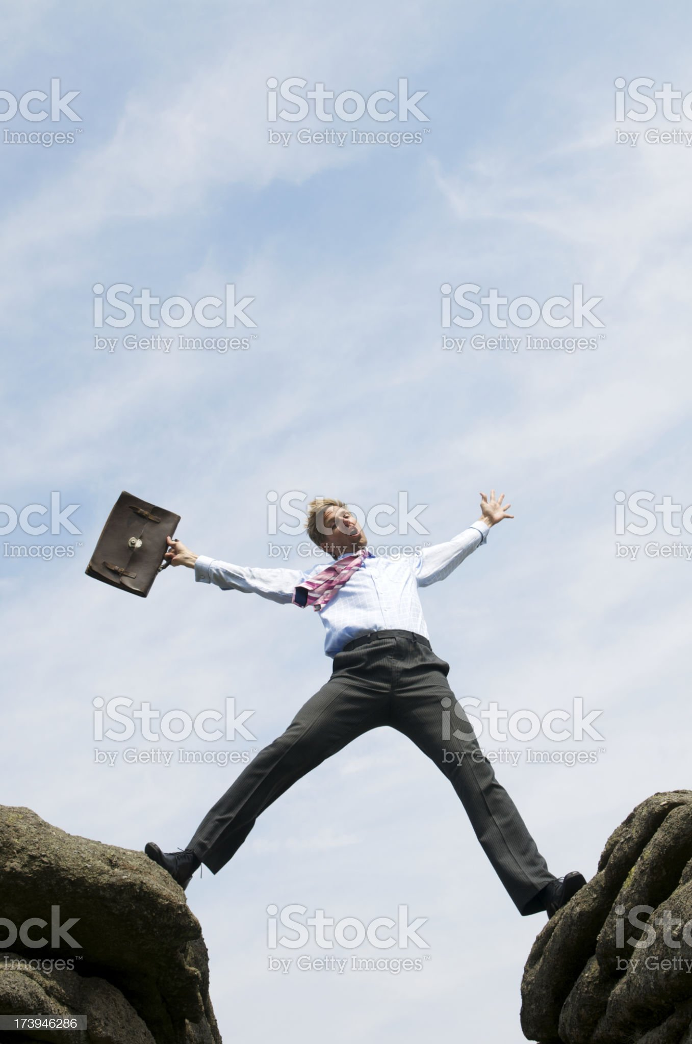Businessman Straddles a Valley between Two Rocks royalty-free stock photo