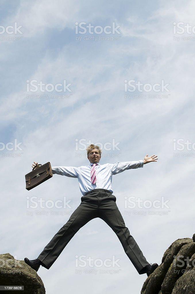 Businessman Straddles the Gap between Rocks stock photo