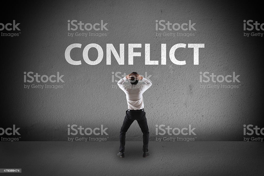 Businessman stress look at conflict on wall stock photo