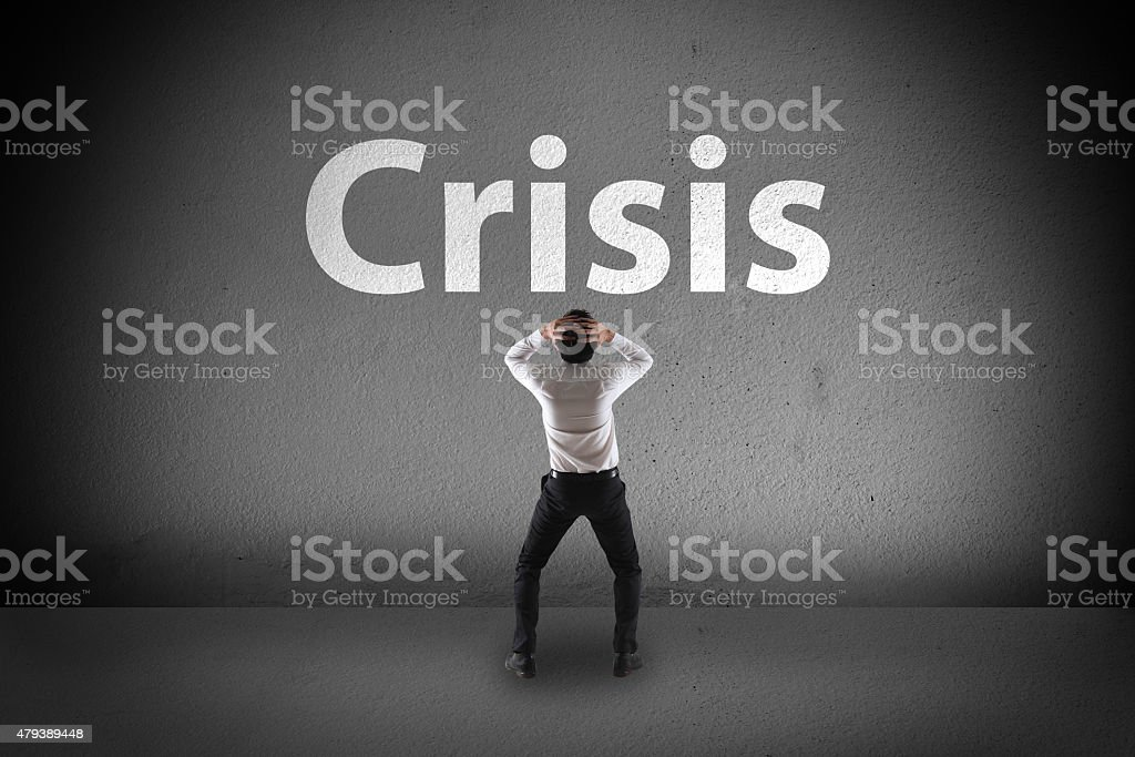 Businessman stress look at crisis on wall stock photo