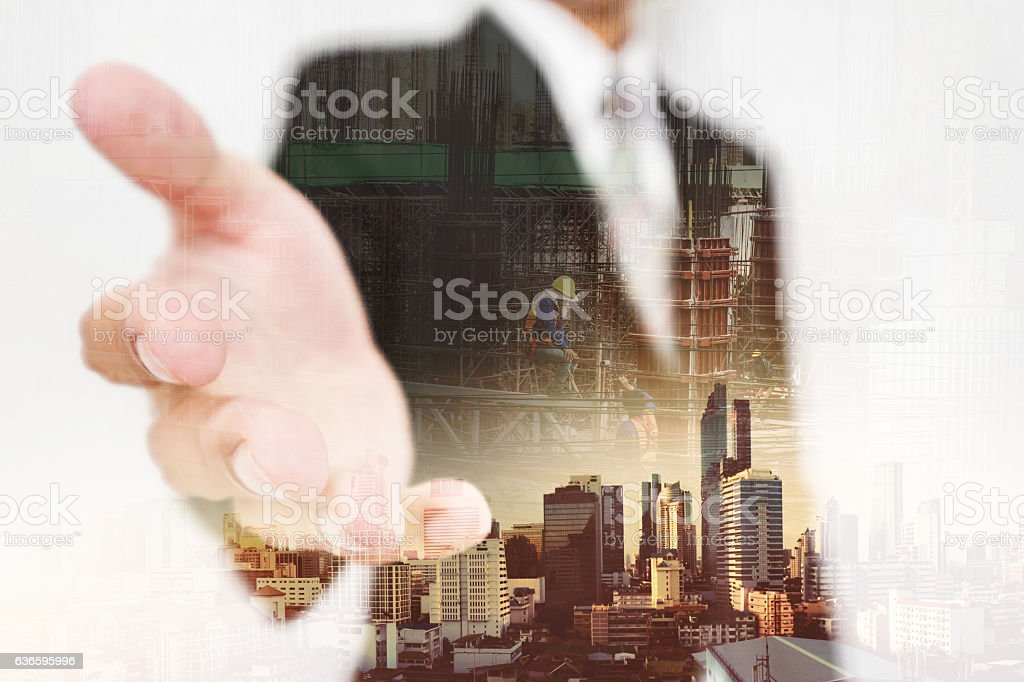 Businessman stretching hand, with double-exposure city and real-estate site construction stock photo