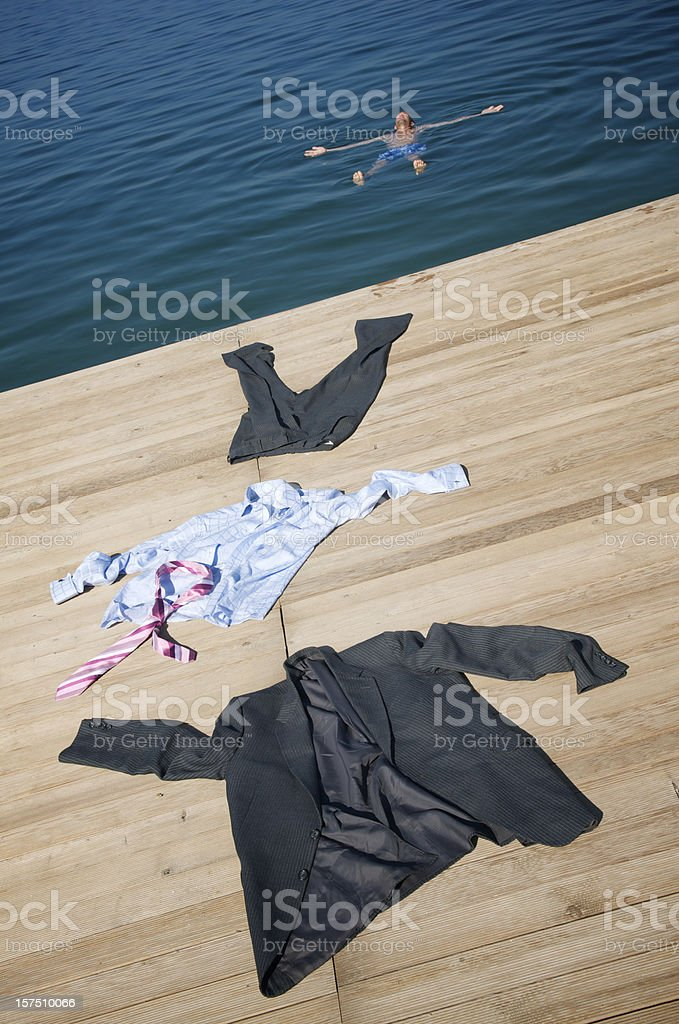 Businessman Strips off Suit and Floats in Water royalty-free stock photo