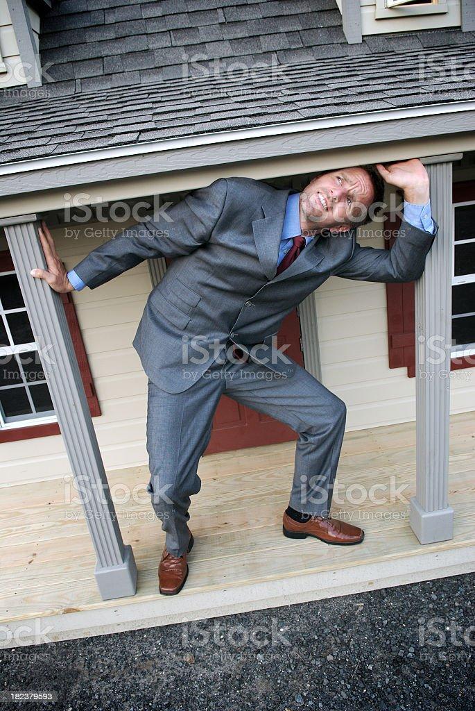 Businessman Struggles under Shrinking House stock photo