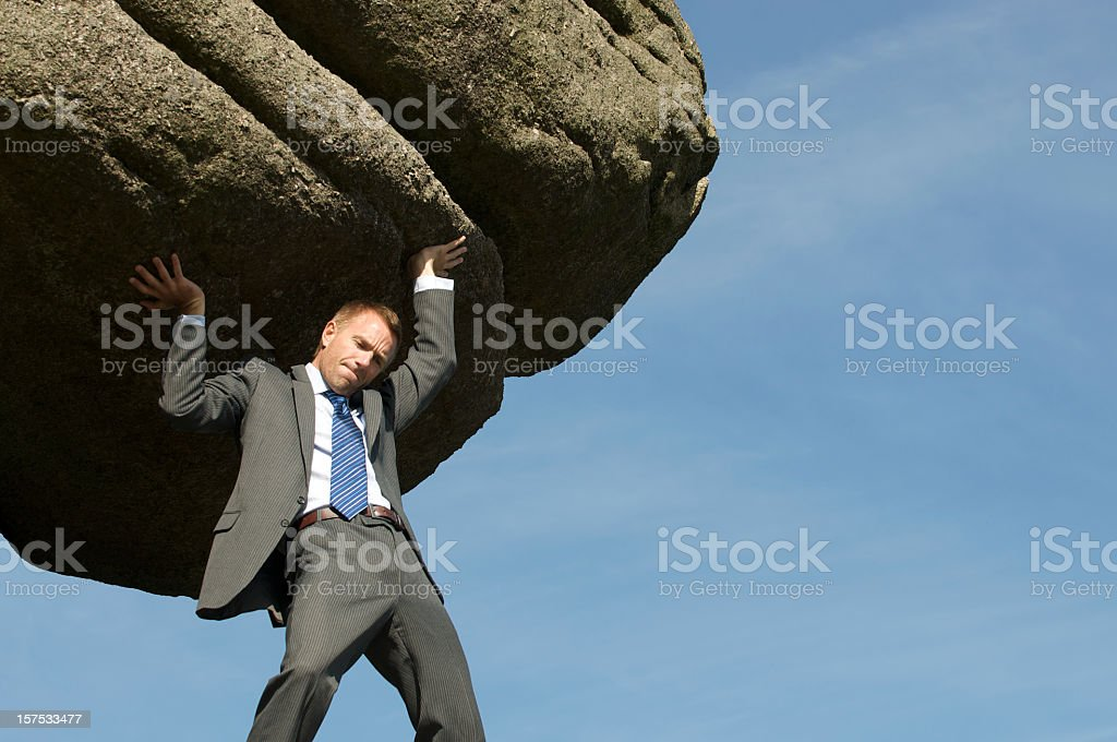 Businessman Struggling Lifting Massive Boulder Outdoors in Sky stock photo