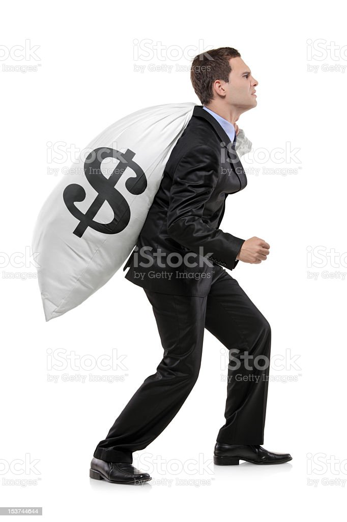 Businessman struggling to carry heavy bag of money royalty-free stock photo