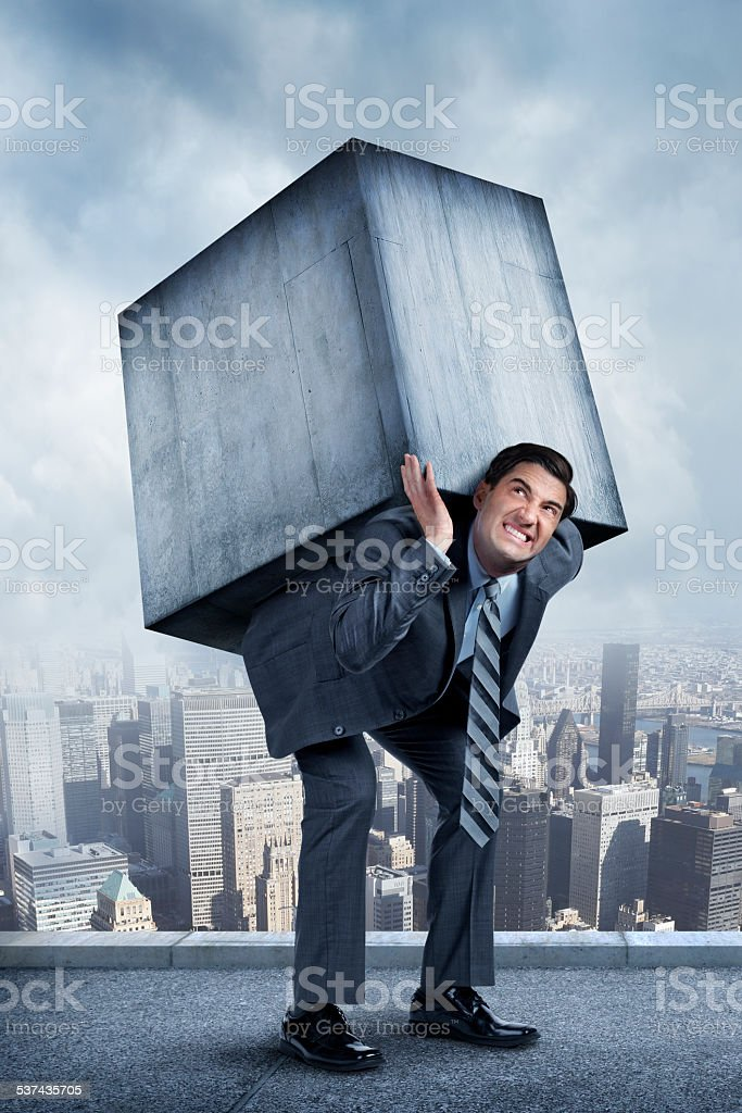 Businessman Struggling Under Weight Of Concrete Block stock photo