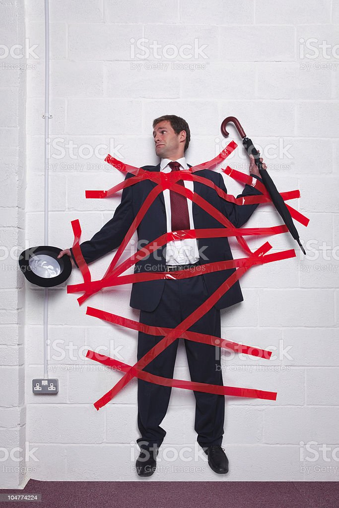 Businessman stuck to wall with red tape stock photo