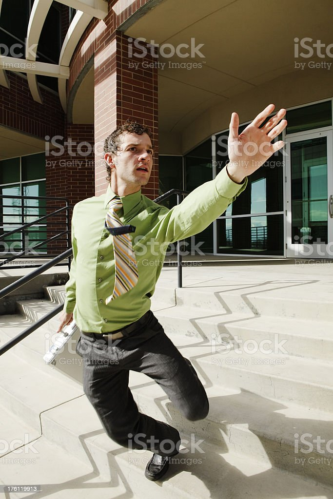 Businessman stumbling down stairs, waving hand to catch a ride stock photo