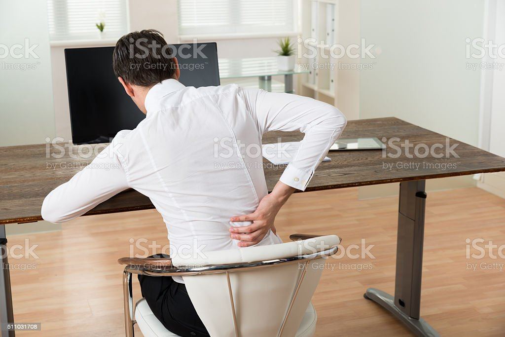 Businessman Suffering From Backache At Desk stock photo