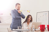 Businessman supervising his female assistant's work on laptop co