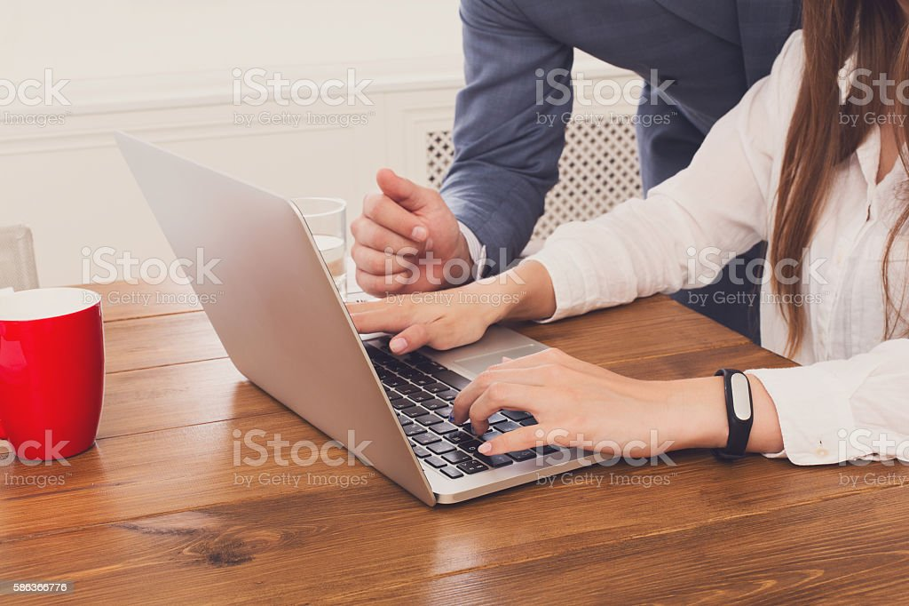 Businessman supervising secretary work on laptop, closeup of hands, unrecognizable stock photo