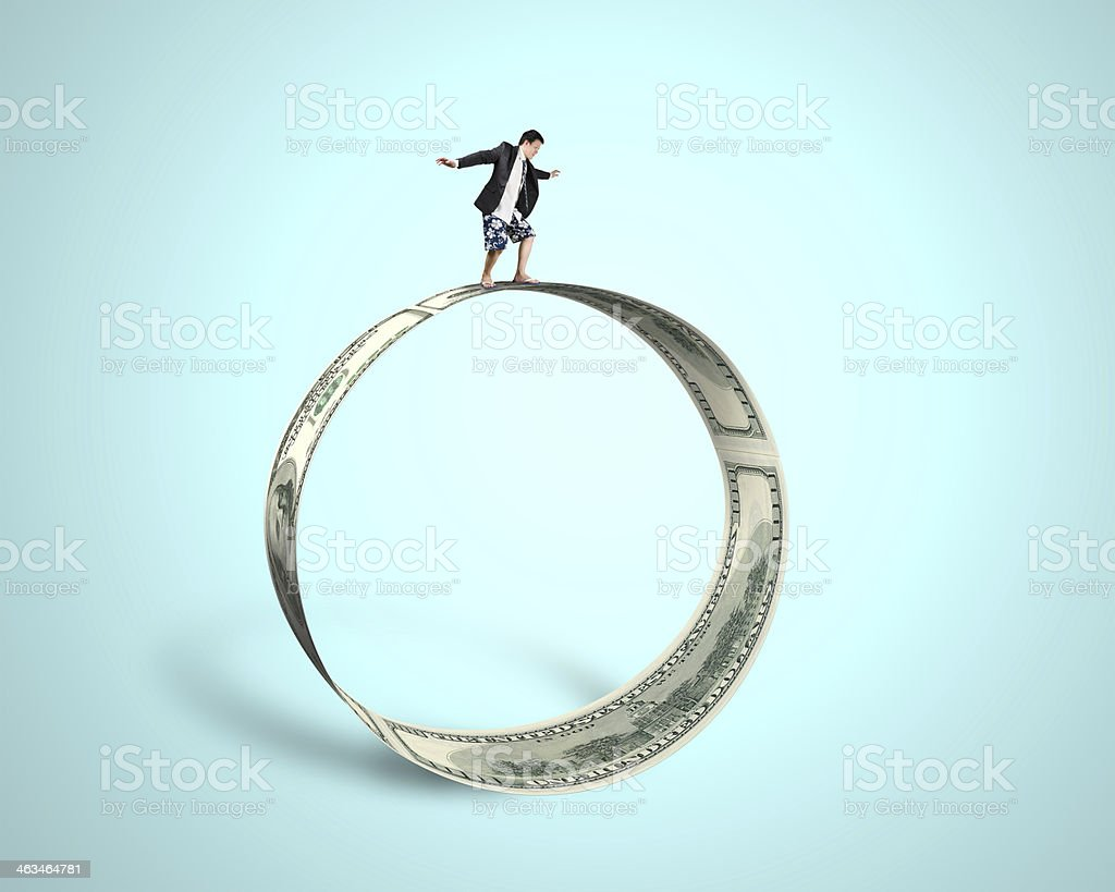 Businessman surfing and balancing on large money circle in green royalty-free stock photo